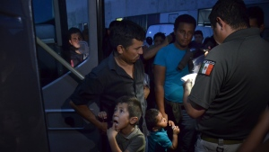 Migrants have their names checked by immigration officials as they board a bus that will take them to the city of Monterrey, outside at an immigration center on the International Bridge 1, in Nuevo Laredo, Mexico, Tuesday, July 16, 2019. A U.S. policy to make asylum seekers wait in Mexico while their cases wind through clogged U.S. immigration courts has also expanded to the violent city of Nuevo Laredo. (AP Photo/Salvador Gonzalez)