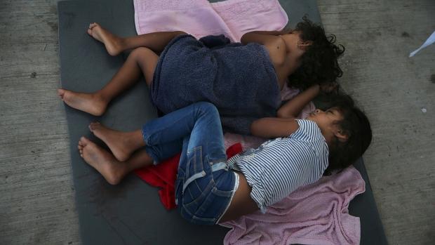 Migrant children sleep on a mattress
