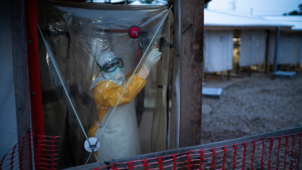 A health worker wearing a protective suit enters an isolation pod to treat a patient at a treatment center in Beni, Congo DRC, Saturday July 13, 2019. (AP / Jerome Delay)