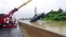 Crane pulls car off flooded Hwy. 401