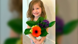 This Feb. 14, 2019 photo provided by her uncle David Smith shows 6-year-old Aria Hill posing with flowers near Eagle Mountain in northern Utah during a family trip. (David Smith via AP)