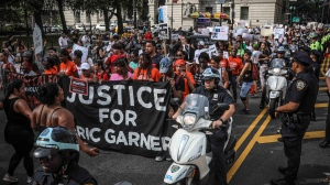 A rally marches in protest against the decision by federal prosecutors not to bring civil rights charges against NYPD officer Daniel Pantaleo for the 2014 chokehold death of Eric Garner, Wednesday July 17, 2019. (AP Photo/Bebeto Matthews)