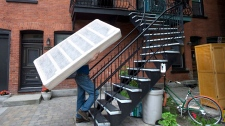 "A man carries a boxspring up a set of stairs on what has become known as ""Moving Day,"" in Montreal, on July 1, 2013. A new analysis of the country's rental market suggests that a minimum-wage worker can't afford the rent in all but a few neighbourhoods nationwide, and raises questions about a promised federal rent supplement. THE CANADIAN PRESS/Graham Hughes"