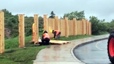Workers remove a fence at Signal Hill, N.L.