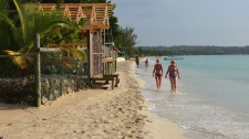 In this Sept. 14, 2014 photo, sunbathers walk along resort-lined crescent beach in Negril in western Jamaica. (THE CANADIAN PRESS / AP-David McFadden)
