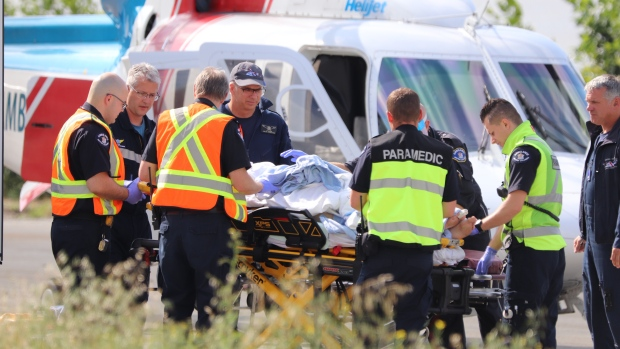 First responders are seen working on a patient after a car went over an embankment in Maple Ridge on July 18, 2019. (Shane MacKichan)