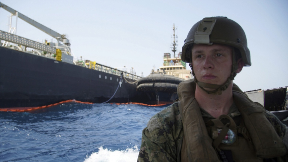 The damaged Panama-flagged, Japanese owned oil tanker Kokuka Courageous, that the U.S. Navy says was damaged by a limpet mine, is seen behind a U.S. sailor, during a trip organized by the Navy for journalists, on June 19, 2019. (Fay Abuelgasim / AP)