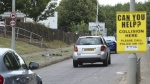 A sign appeals for witnesses at the scene of a crash during a gathering of car enthusiasts in Stevenage, England. (Yui Mok/PA via AP)