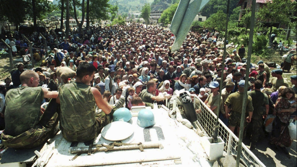 Dutch UN peacekeepers sit on top of an armored personnel carrier while Muslim refugees from Srebrenica, eastern Bosnia, gather in the village of Potocari, on July 13, 1995. (AP)