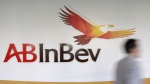 A man walks past the AB InBev logos, in Leuven, Belgium, on March 3, 2011. (Yves Logghe / AP)