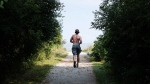 A man runs through Humber Bay Shores in Toronto on Tuesday, August 7, 2018. THE CANADIAN PRESS/Christopher Katsarov