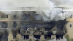 Firefighters work as smoke billows from fire at a three-storey building of Kyoto Animation in a fire in Kyoto, western Japan, on July 18, 2019. (Kyodo News via AP)