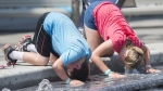 "A boy and girl dunk their heads in a water fountain during a heat wave in Montreal, Monday, in this file photo dated July 2, 2018. A large swath of Eastern Canada is scorching under temperatures that, with the humidex, are expected to reach 40 C or higher on Friday and Saturday in some regions, in what is being called a ""heat dome"". THE CANADIAN PRESS/Graham Hughes"