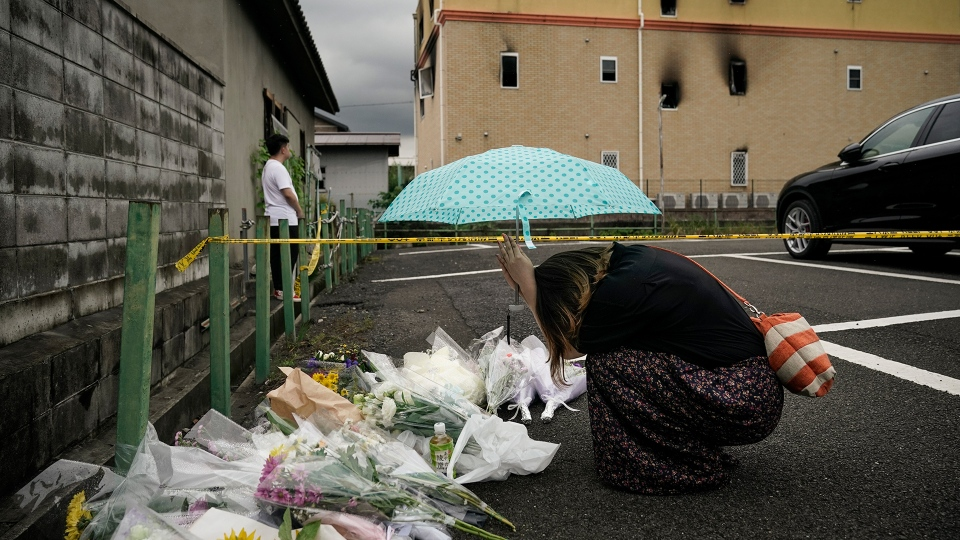 A woman prays at a makeshift memorial to honor the victims of Thursday's fire at the Kyoto Animation Studio building, background, Friday, July 19, 2019, in Kyoto, Japan. (AP / Jae C. Hong)