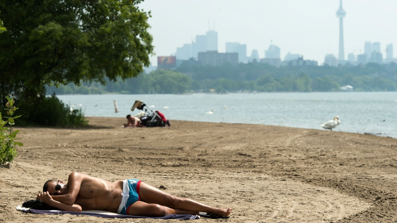 A man sleeps on the sandy beach along Lake Ontario in the extreme heat in Toronto on Friday, July 19, 2019. THE CANADIAN PRESS/Nathan Denette