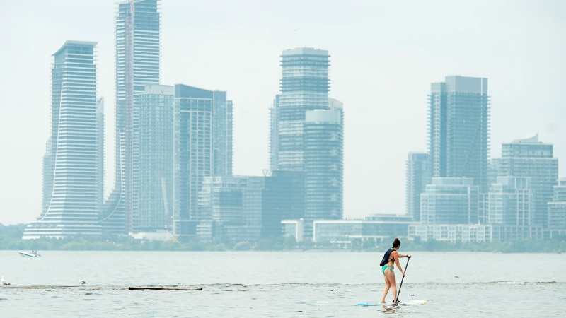 A women paddle boards along Lake Ontario in the extreme heat in Toronto on Friday, July 19, 2019. THE CANADIAN PRESS/Nathan Denette