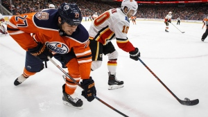Calgary Flames' Derek Ryan (10) and Edmonton Oilers' Milan Lucic (27) battle for the puck during second period NHL action in Edmonton on Saturday, Jan. 19, 2019. THE CANADIAN PRESS/Jason Franson