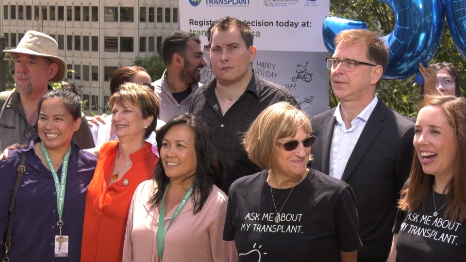 B.C. Health Minister Adrian Dix (back right) is seen at event marking 50 years of organ transplants in B.C. on July 19, 2019.