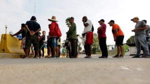 In this April 30, 2019, file photo, migrants seeking asylum in the United States line up for a meal provided by volunteers near the international bridge in Matamoros, Mexico. (AP Photo/Eric Gay, File)