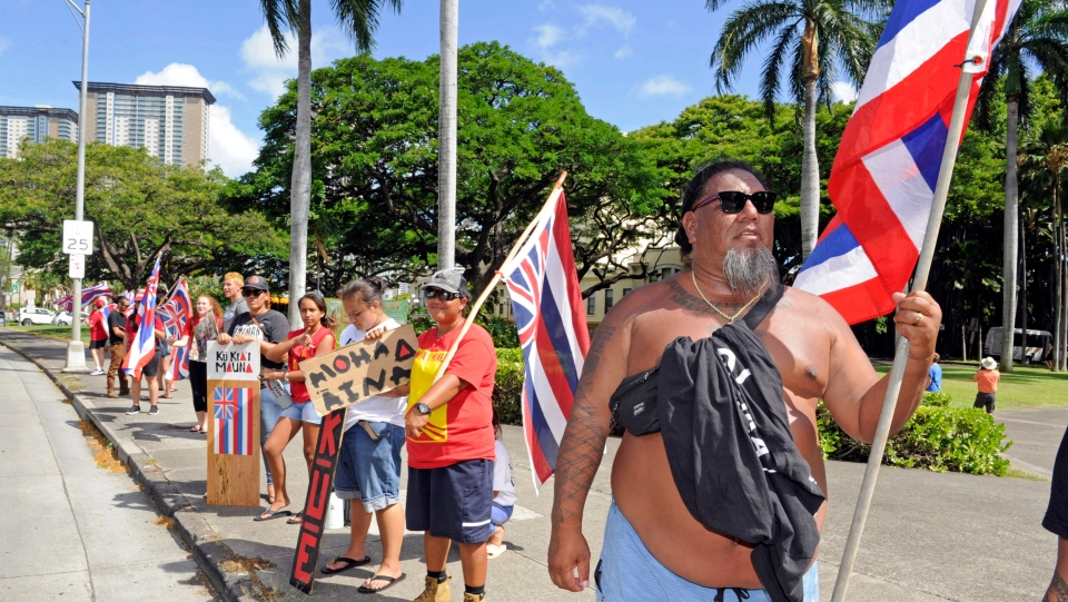Kimo Leong, of Waianae on the Big Island of Hawaii, right, is among demonstrators protesting the Thirty Meter Telescope proposed for Mauna Kea on his home island, on King Street in downtown Honolulu Friday, July 19, 2019. (Craig T. Kojima/Honolulu Star-Advertiser via AP)