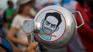 "A demonstrator bangs on a pot that has a cartoon drawing of Governor Ricardo Rossello and text the reads in Spanish ""Quit Ricky"" as people gather to protest against Gov. Rossello, in San Juan, Puerto Rico, Friday, July 19, 2019. Protesters are demanding Rossello step down for his involvement in a private chat in which he used profanities to describe an ex-New York City councilwoman and a federal control board overseeing the island's finance. (AP Photo/ Dennis M. Rivera Pichardo)"