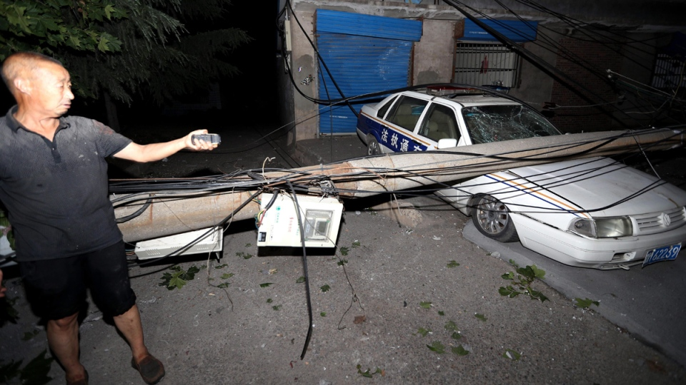 A resident points to a car smashed by a fallen electricity pole in the aftermath of a blast at a nearby gas plant in Yima, China, on July 20, 2019. (Chinatopix via AP)