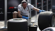 A Mercedes team mechanic washes tires