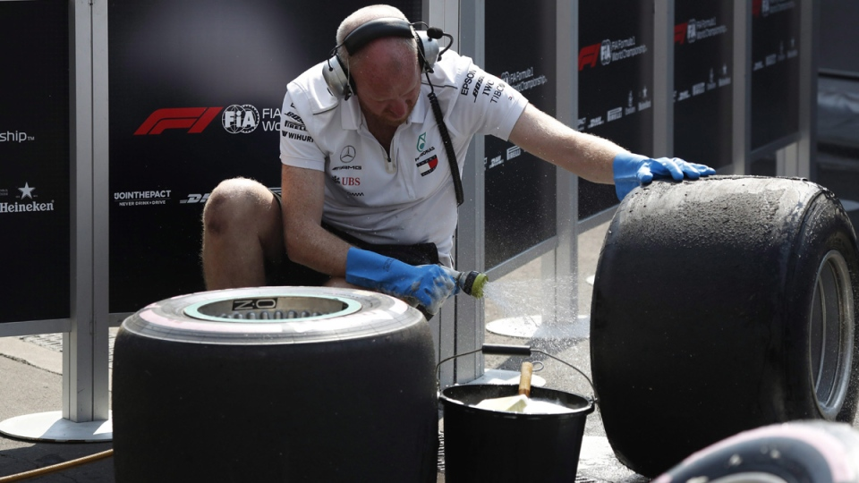 A Mercedes team mechanic washes tires after the first training session prior to the Formula One Mexico Grand Prix auto race at the Hermanos Rodriguez racetrack in Mexico City, on Oct. 26, 2018. (Moises Castillo / AP)