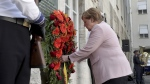 German Chancellor Angela Merkel adjusts a wreath during a memorial event at the Defence Ministry in Berlin, Germany, on July 20, 2019. (Michael Sohn / AP)