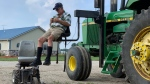 Farmer Mark Hosier, 58, uses a lift to get into a tractor on his farm in Alexandria, Ind., on July 10, 2019. (Andrew Soregel via AP)