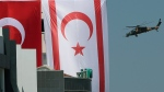 Turkish, right, and Turkish Cypriot breakaway flags, on a building as a Turkish military helicopter flies during a military parade marking the 45th anniversary of the 1974 Turkish invasion in the Turkish occupied area of the divided capital Nicosia, Cyprus, Saturday, July 20, 2019. Cyprus was split into Greek Cypriot south and Turkish Cypriot north in 1974 when Turkey invaded in response to a coup by supporters of a union with Greece. (AP Photo/Petros Karadjias)