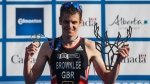 Jonathan Brownlee of Great Britain holds up the trophies after the win of the Elite Men's event at the ITU World Triathlon Series in Edmonton on Saturday, July 20, 2019. (THE CANADIAN PRESS / Jason Franson)