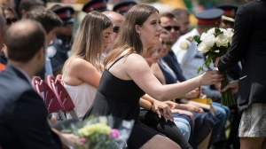 Quinn Fallon prepares to lay flowers in honour of her older sister, Reese Fallon, who was killed during the Danforth shooting during a commemoration at Withrow Park in Toronto, on Sunday, July 21, 2019. (THE CANADIAN PRESS/ Tijana Martin)