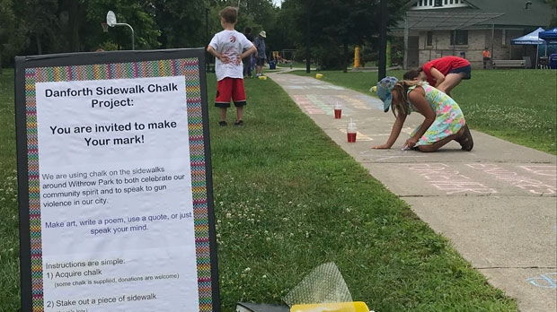 Toronto residents were encouraged to write messages of hope on the sidewalk as part of the commemorative ceremony held to mark one year since the Danforth shooting. (Phil Fraboni/CTV News Toronto)