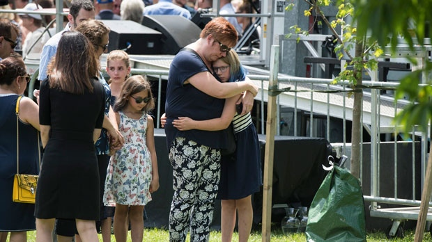 Friends and family members honour the life of Julianna Kozis, near a tree planted in her honour, following the Danforth shooting commemoration at Withrow Park in Toronto on Sunday, July 21, 2019. (THE CANADIAN PRESS/ Tijana Martin)
