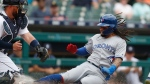 Toronto Blue Jays' Freddy Galvis, right, beats the throw to Detroit Tigers catcher Bobby Wilson to score from first on a double by teammate Lourdes Gurriel Jr. during the first inning of a baseball game, Sunday, July 21, 2019, in Detroit. (AP Photo/Carlos Osorio)