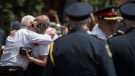 Claudine Debeaumont, the mother of Reese Fallon, who was killed during the Danforth shooting one year ago, receives a hug during commemoration of the Danforth shooting at Withrow Park in Toronto on Sunday, July 21, 2019. (THE CANADIAN PRESS/ Tijana Martin)