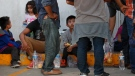 Migrants wait to board a bus that will take them to Monterrey, from an immigration center in Nuevo Laredo, Mexico, Thursday, July 18, 2019. (AP Photo/Marco Ugarte)