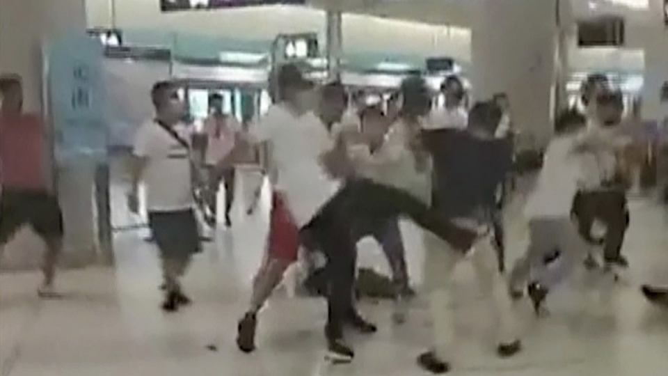 In this image from video, masked assailants and protesters clash at Yuen Long MTR train station in Hong Kong, on July 21, 2019. (Lam Cheuk-ting via AP)
