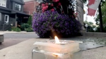 A candle at Alexander the Great Parkette is lit on July 22, 2019 to honour the victims of the Danforth attack one year after. (CTV News Toronto / Francis Gibb)