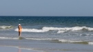A woman stands in the surf on the beach in Oak Island, N.C., Monday, June 15, 2015. (AP Photo/Chuck Burton)