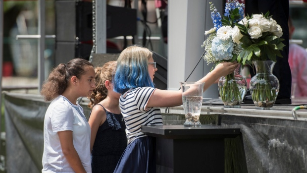 Family members and friends of the late Julianna Kozis, place a bouquet of flowers on the stage during a a commemoration of the Danforthshooting from one year ago, at Withrow Park in Toronto on Sunday, July 21, 2019. (THE CANADIAN PRESS / Tijana Martin)