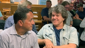 In this Tuesday, July 16, 2019, file photo, Michael Lang, right, Woodstock 50 co-producer and co-founder, sits in Vernon Town Hall before a planning board hearing in Vernon, N.Y., for his appeal to grant a permit for the Woodstock 50 music festival. (Edward Harris/Observer-Dispatch via AP)
