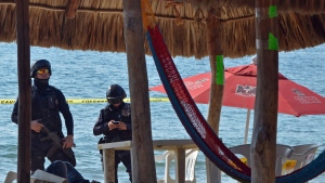 FILE - In this Jan. 6, 2017 file photo, state police inspect the site where two men were shot at the Tamarindos beach in the port city of Acapulco, Mexico. (AP Photo/Bernandino Hernandez, File)