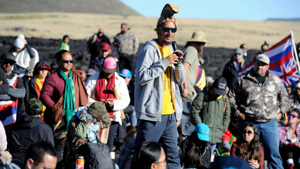 Kaho'okahi Kanuha, wearing a traditional Hawaiian battle helmet, addresses a group of protesters who are continuing their opposition vigil against the construction of the Thirty Meter Telescope at Mauna Kea on the Big Island of Hawaii Friday, July 19, 2019. (Bruce Asato/Honolulu Star-Advertiser via AP)