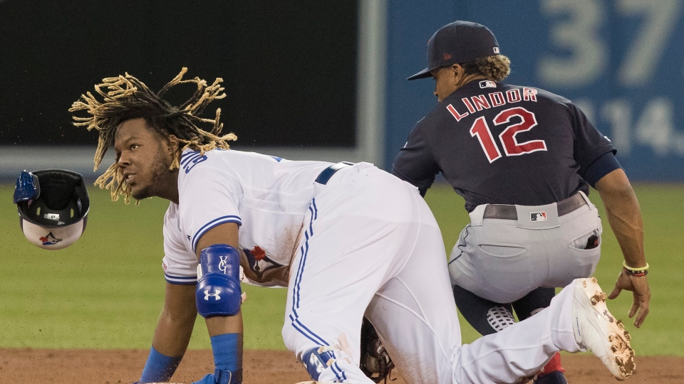 Toronto Blue Jays' Vladimir Guerrero Jr. is out at second base trying to stretch a single into a double as Cleveland Indians' Francisco Lindor applies the tag during second inning American League MLB baseball action in Toronto, Monday, July 22, 2019. THE CANADIAN PRESS/Fred Thornhill