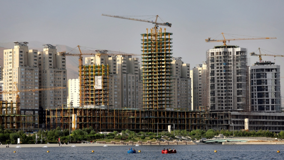 This July 6, 2019 photo shows residential towers in District 22, that consists of apartment high-rises and shopping malls arranged around an artificial lake called Chitgar, under construction on the northwestern edge of Tehran, Iran. Iran's large middle class has been hit hard by the fallout from unprecedented U.S. sanctions, including the collapse of the national currency. (AP Photo/Ebrahim Noroozi)