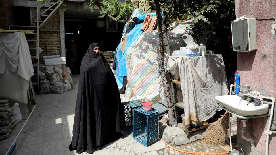 In this Saturday, July 6, 2019 photo, Zeinab Ebrahimi, 56, stands at the courtyard of her house which is under renovation, in the old District 12 of Tehran, Iran. The spike in housing prices has uprooted tenants and made home ownership unattainable for most. (AP Photo/Ebrahim Noroozi)