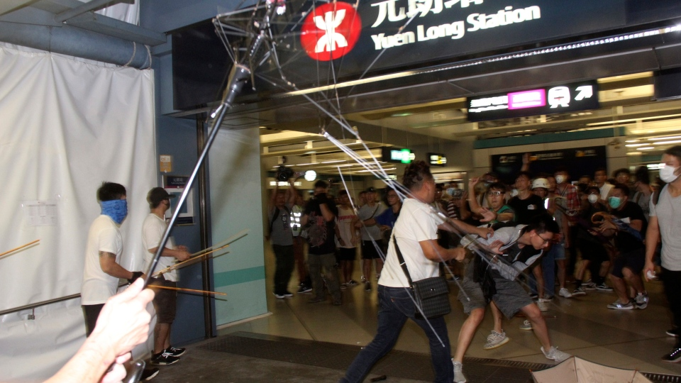 In this Sunday, July 21, 2019, photo, thugs in white shirts armed with metal rods and wooden poles attack commuters at a subway station in New Territory in Hong Kong. Neither side wants China's People's Liberation Army to step in, but the growing chaos and what China will see as a direct challenge to its authority seems to raise the risks.(Apple Daily via AP)