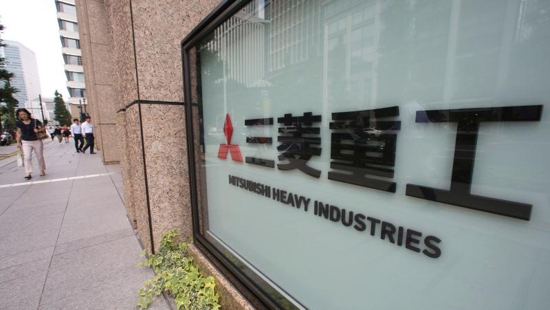 People walk past the company sign of the Mitsubishi Heavy Industries in Tokyo, on July 23, 2019. (Koji Sasahara / AP)